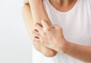 kvinna kliar sig på armen